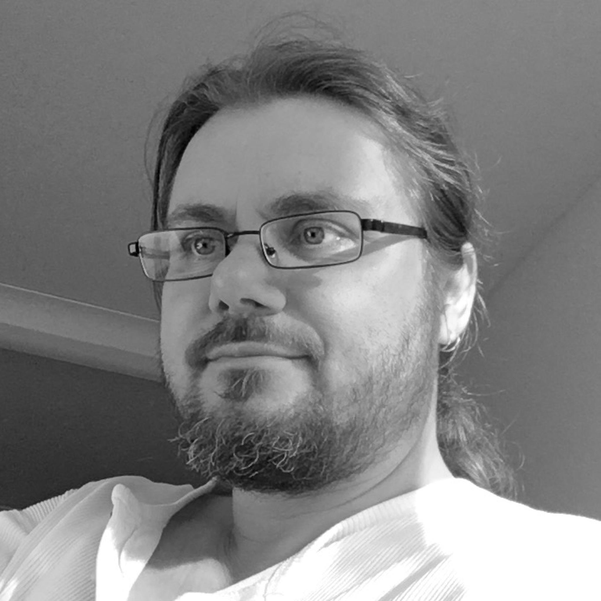 schwarz-weiß-Portrait: 45jähriger Mann mit Vollbart und Brille
